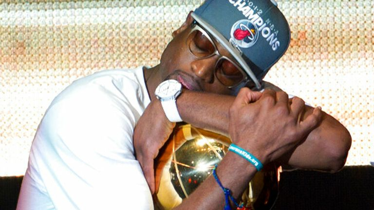 Miami Heat's Dwyane Wade hugs the NBA Championship trophy after the June 25, 2012 public celebration. (AP Photo/J Pat Carter)
