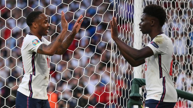 England's Raheem Sterling celebrates after scoring his side's opening goal with England's Bukayo Saka scores his side's opening goal during the Euro 2020 soccer semifinal match between England and Denmark at Wembley