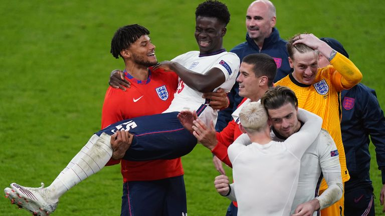 Tyrone Mings carries Bukayo Saka as they celebrate winning the Euro 2020 semi-final