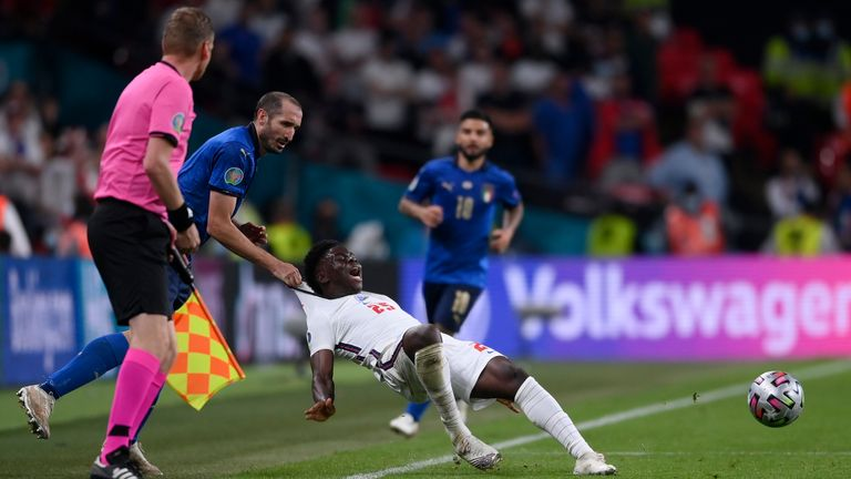 Italy's Giorgio Chiellini, left, stops England's Bukayo Saka during the Euro 2020 soccer final match between England and Italy at Wembley