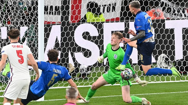 England's goalkeeper Jordan Pickford makes a save in front of Italy's Federico Bernardeschi during the Euro 2020 final soccer match between Italy and England at Wembley