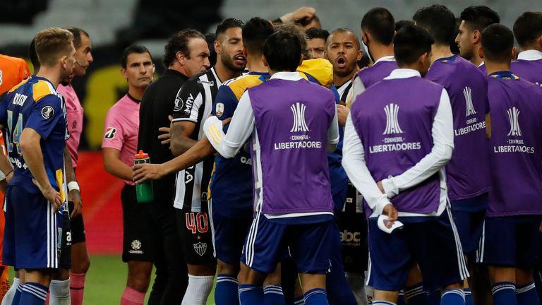 Players of Boca Juniors and Atletico Mineiro argue as referee Esteban Ostojich checks the VAR system during a Copa Libertadores match