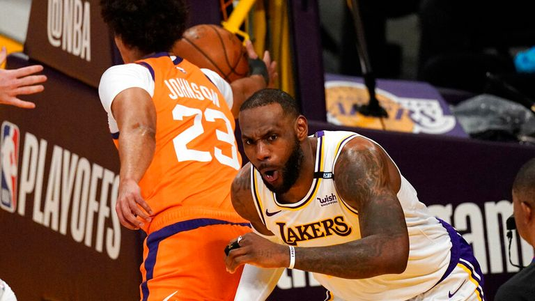 Los Angeles Lakers forward LeBron James, right, reacts after dunking as Phoenix Suns forward Cameron Johnson takes the ball during the first half in Game 4 of an NBA basketball first-round playoff series Sunday, May 30, 2021, in Los Angeles. (AP Photo/Mark J. Terrill)