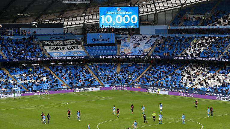 Fans are seen as an attendance of 10,000 spectators is announced during the Premier League match between Manchester City and Everton at Etihad Stadium