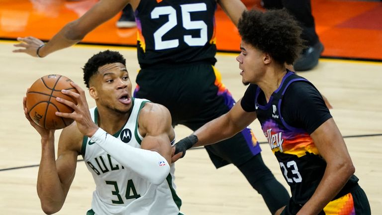 Milwaukee Bucks forward Giannis Antetokounmpo (34) looks to pass as Phoenix Suns forward Cameron Johnson (23)defends during the second half of Game 1 of basketball's NBA Finals, Tuesday, July 6, 2021, in Phoenix.