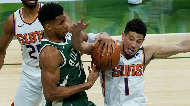 Milwaukee Bucks forward Giannis Antetokounmpo (34) and Phoenix Suns guard Devin Booker (1) battle for a loose ball during the second half of Game 3 of basketball's NBA Finals in Milwaukee, Sunday, July 11, 2021.