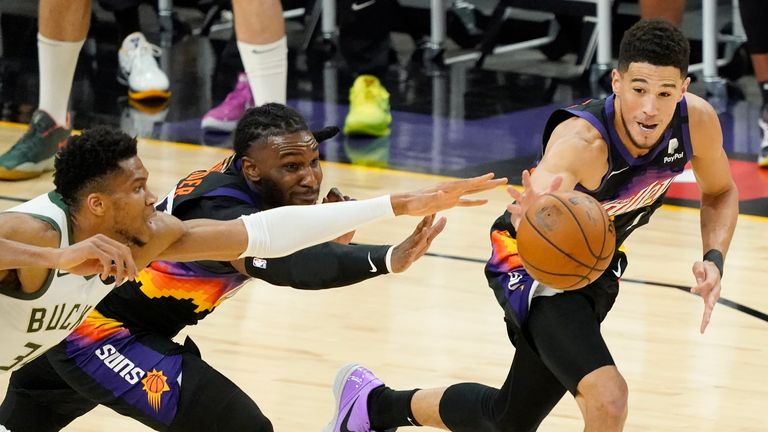 Phoenix Suns guard Devin Booker, right, reaches for the ball in front of forward Jae Crowder, middle, and Milwaukee Bucks forward Giannis Antetokounmpo, left, during the first half of Game 5 of basketball...s NBA Finals, Saturday, July 17, 2021, in Phoenix. (AP Photo/Matt York)