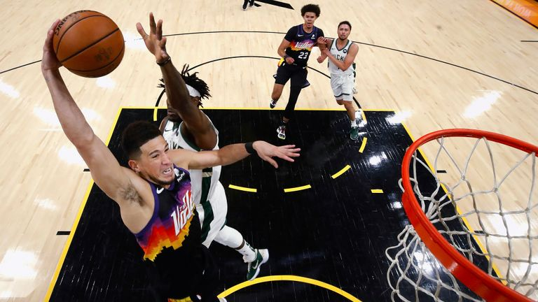 Phoenix Suns' Devin Booker goes up for a dunk next to Milwaukee Bucks' Jrue Holiday (21) during the first half of Game 2 of basketball's NBA Finals, Thursday, July 8, 2021, in Phoenix. (Christian Petersen/Pool Photo via AP)