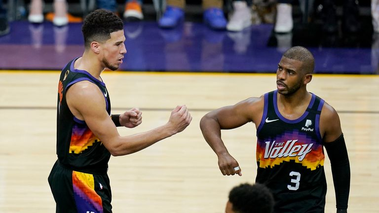 Phoenix Suns guard Devin Booker, left, reacts with guard Chris Paul (3) during the first half of Game 2 of basketball's NBA Finals against the Milwaukee Bucks, Thursday, July 8, 2021, in Phoenix. (AP Photo/Ross D. Franklin)