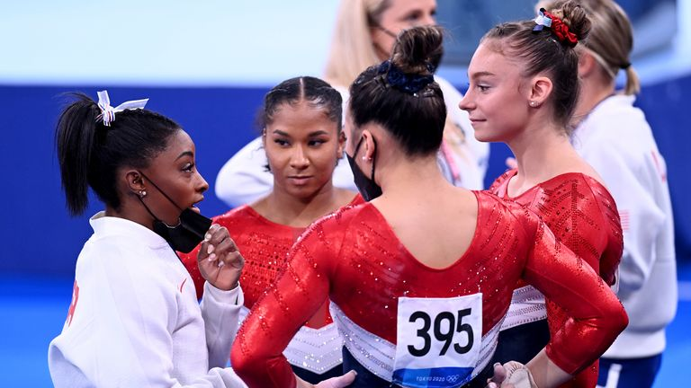 Simone Biles speaks to her United States teammates after she withdraws from the women's team final