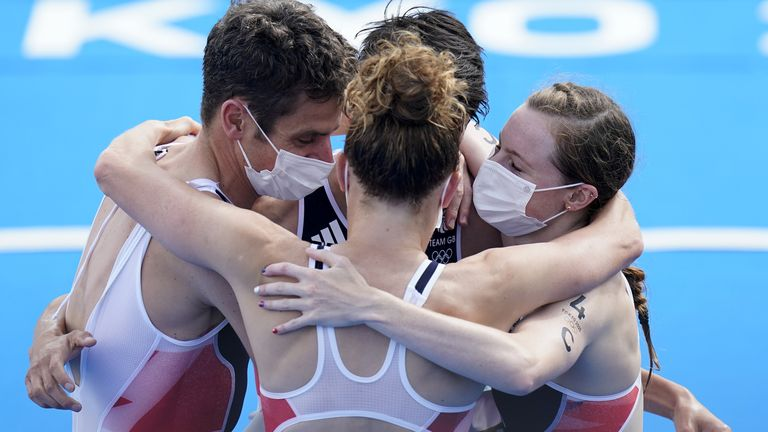 The mixed triathlon team embrace eachother after claiming the gold medal