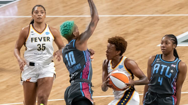 Indiana Fever guard Danielle Robinson (3) drives between Atlanta Dream guards Aari McDonald (4) and Courtney Williams (10) during a WNBA basketball game, Sunday, July 11, 2021, in College Park, Ga.