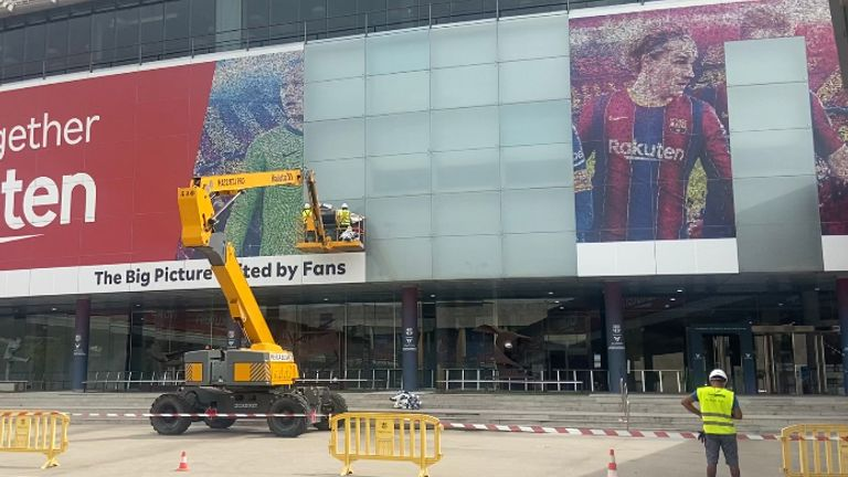 Workers in Barcelona remove a huge image of their former player Lionel Messi from the side of the Nou Camp.