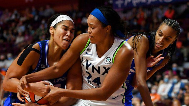 Connecticut Sun center Brionna Jones takes the ball away from Minnesota Lynx forward Napheesa Collier (24) as Sun's DeWanna Bonner defends during a WNBA basketball game