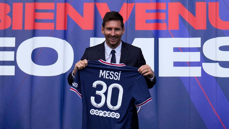 Lionel Messi pictured holding his PSG jersey after a press conference
