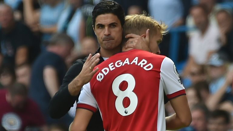 Mikel Arteta embraces Martin Odegaard as he comes off the pitch (AP)