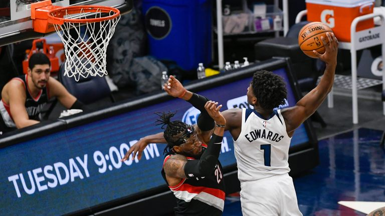 Minnesota Timberwolves guard Anthony Edwards (1) dunks the ball over Portland Trail Blazers forward Robert Covington during the second half of an NBA basketball game Sunday, March 14, 2021, in Minneapolis. Timberwolves won 114-112.