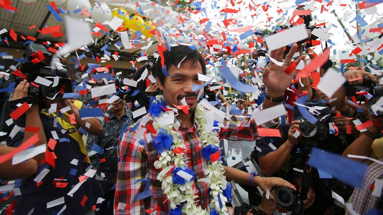 Filipino boxing hero Manny Pacquiao waves as confetti falls during a heroes welcome at the financial district of Makati, south of Manila, Philippines on Thursday Nov. 27, 2014. Pacquiao recently defeated Chris Algieri of the United States to win the WBO world welterweight title. (AP Photo/Aaron Favila)