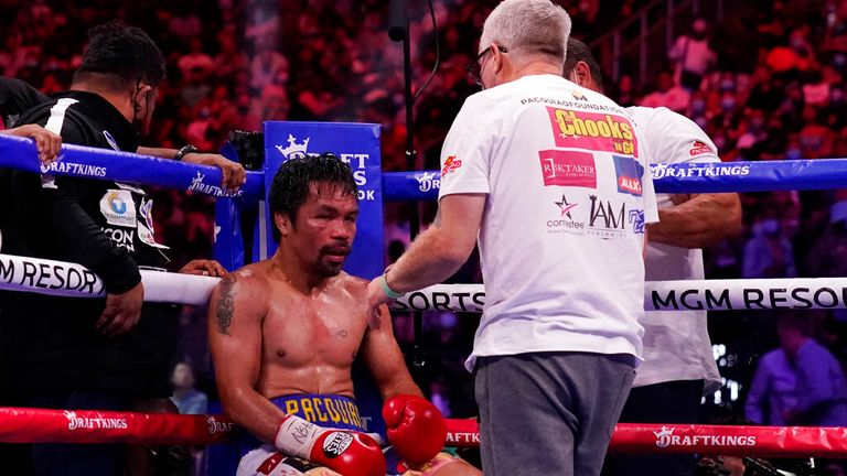 Trainer Freddie Roach speaks to Manny Pacquiao, of the Philippines, between rounds against Yordenis Ugas, of Cuba, in a welterweight championship boxing match Saturday, Aug.  21, 2021, in Las Vegas.  (AP Photo/John Locher)