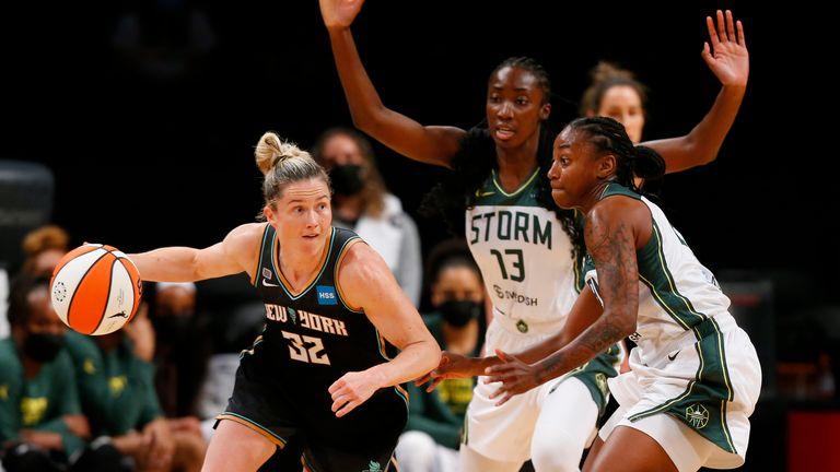 New York Liberty guard Sami Whitcomb dribbles the ball against Seattle Storm defenders Ezi Magbegor and Jewell Loyd
