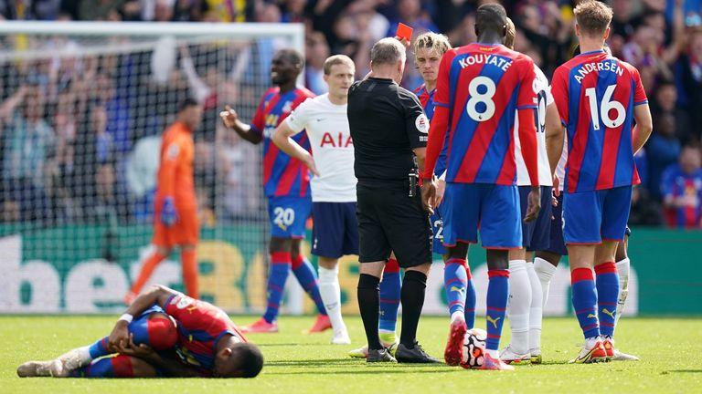 El árbitro Jon Moss expulsa a Japhet Tanganga por un desafío sobre Jordan Ayew