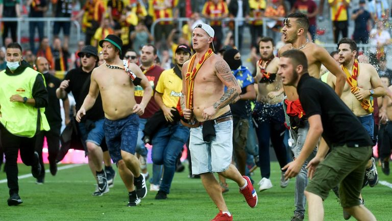 Lens fans ran onto the pitch at half-time in their derby win over Lille, leading to a half-hour delay