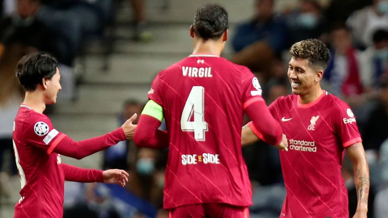 Liverpool's Roberto Firmino, right, celebrates after scoring his side's fifth goal during the Champions League group B soccer match between FC Porto and Liverpool at the Dragao stadium
