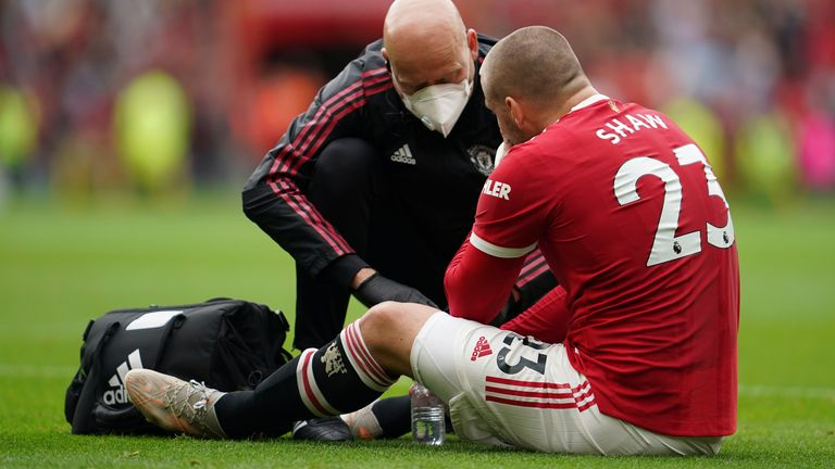 Luke Shaw receives medical treatment before leaving the field (AP)