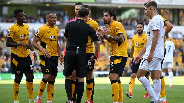 Conor Coady, Ruben Neves y sus compañeros de los Wolves rodean al árbitro Darren England en protesta por el penalti a Brentford
