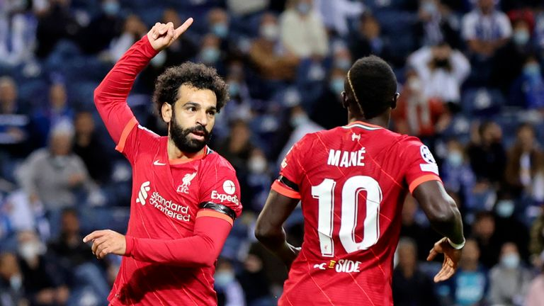 Liverpool's Mohamed Salah, center, celebrates after scoring the opening goal during the Champions League group B soccer match between FC Porto and Liverpool at the Dragao stadium