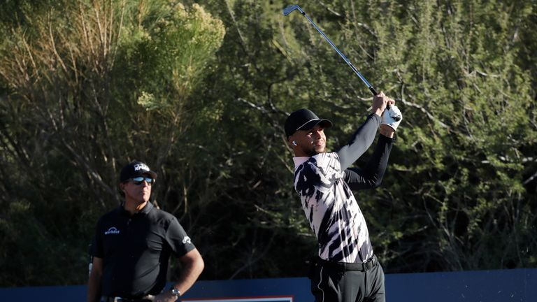 Curry plays his shot from the ninth tee as Phil Mickelson looks on during The Match: Champions For Change at Stone Canyon Golf Club