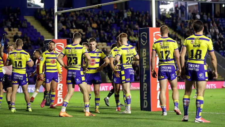 Warrington's players look dejected after conceding a try