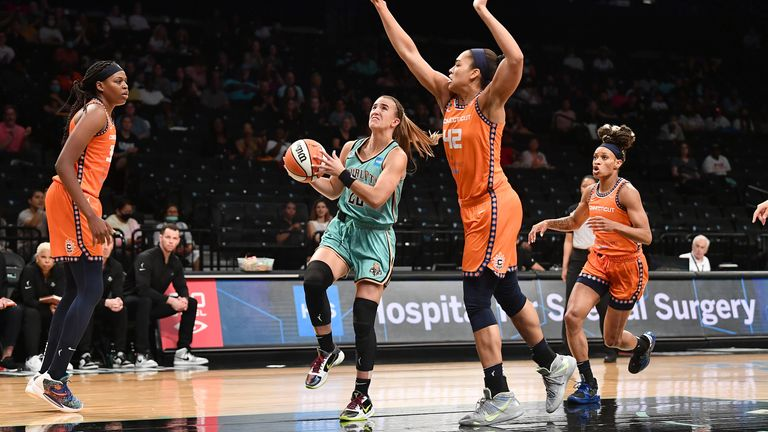 Sabrina Ionescu drives to the basket as Brionna Jones challenges the shot