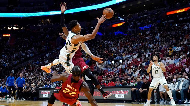 Milwaukee Bucks forward Giannis Antetokounmpo passes the ball to forward Jordan Nwora as Miami Heat center Bam Adebayo and forward Jimmy Butler defend