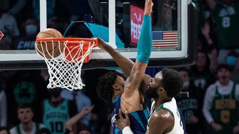Boston Celtics guard Jaylen Brown (7) dunks the ball over Charlotte Hornets forward Miles Bridges (0) during overtime of an NBA basketball game in Charlotte, N.C., Monday, Oct. 25, 2021.