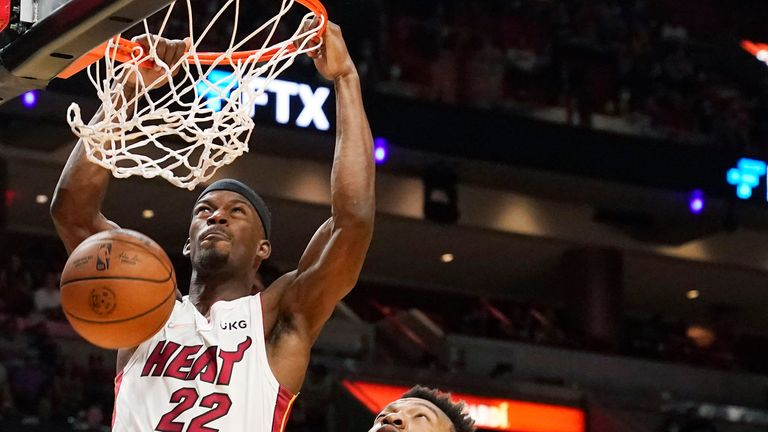 Miami Heat forward Jimmy Butler (22) dunks the ball over Orlando Magic center Wendell Carter Jr. (34) during the first half of an NBA basketball game, Monday, Oct. 25, 2021, in Miami.