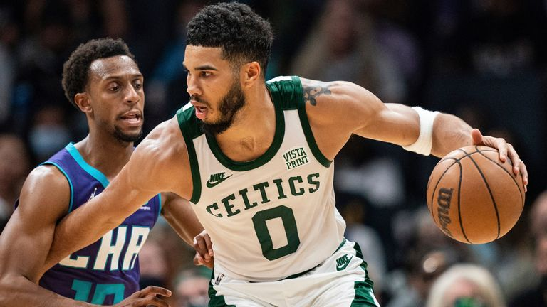 Boston Celtics forward Jayson Tatum (0) shields the ball from Charlotte Hornets guard Ish Smith (10) during the second half of an NBA basketball game in Charlotte, N.C., Monday, Oct. 25, 2021.