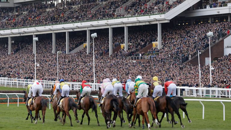 Runners in the opening race pass by the packed main stand during day four of the Cheltenham National Hunt Racing Festival at Cheltenham Racecourse on March 13th 2020 in Gloucestershire (Photo by Tom Jenkins)
