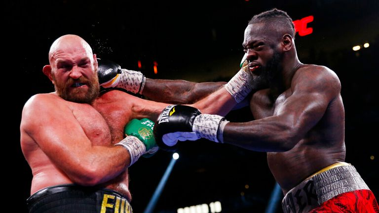 Deontay Wilder, right, and Tyson Fury, of England, trade blows in a heavyweight championship boxing match Saturday, Oct. 9, 2021, in Las Vegas. (AP Photo/Chase Stevens)
