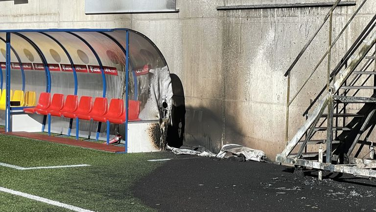 The dugout and a section of pitch are damaged after a fire at the Andorra National Stadium