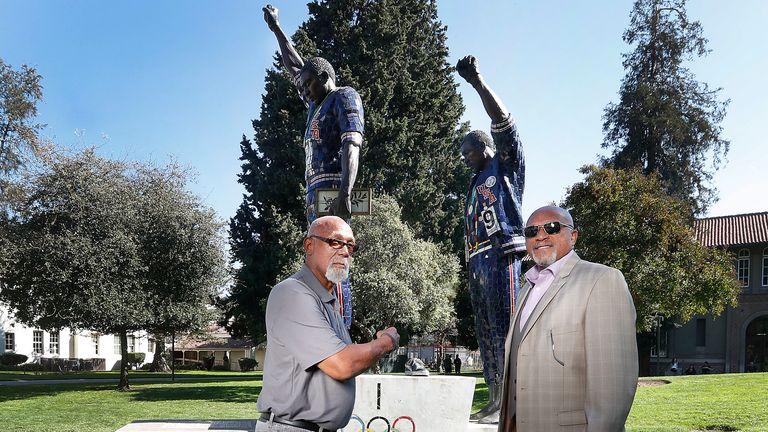 Carlos (left) and Smith in front of a statue that honours their iconic protest at San Jose State University in 2018