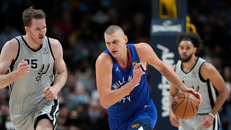 Denver Nuggets center Nikola Jokic picks up a loose ball as San Antonio Spurs center Jakob Poeltl, front left, and guard Derrick White defend during the second half of an NBA basketball game Friday, Oct. 22, 2021, in Denver. The Nuggets won 102-96. (AP Photo/David Zalubowski)