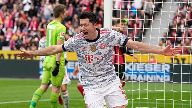 Bayern's Robert Lewandowski celebrates after scoring the opening goal during the German Bundesliga soccer match between Bayer Leverkusen and Bayern Munich in Leverkusen, Germany, Sunday, Oct. 17, 2021.