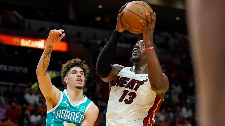 Miami Heat center Bam Adebayo (13) goes to the basket as Charlotte Hornets guard LaMelo Ball defends during the first half of a preseason NBA basketball game, Monday, Oct. 11, 2021, in Miami.