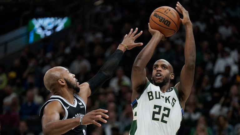 Milwaukee Bucks' Khris Middleton (22) shoots over Brooklyn Nets' Jevon Carter during the first half of an NBA basketball game Tuesday, Oct. 19, 2021, in Milwaukee. (AP Photo/Morry Gash)