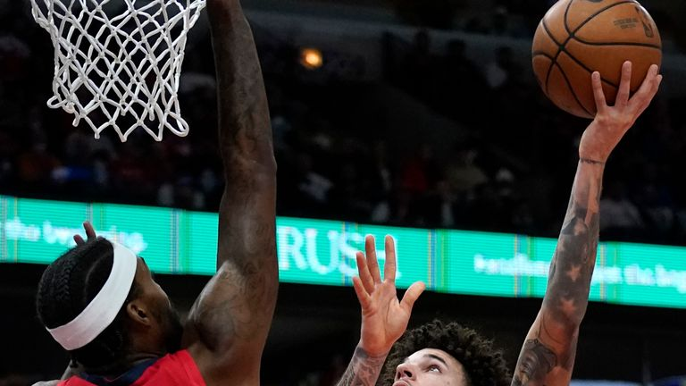 Chicago Bulls guard Lonzo Ball, right, shoots against New Orleans Pelicans forward Naji Marshall during the first half of an NBA basketball game in Chicago, Friday, Oct. 22, 2021. (AP Photo/Nam Y. Huh)