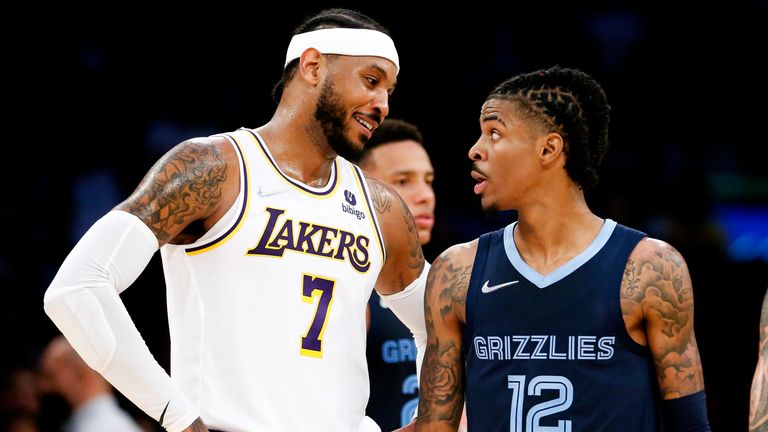 Los Angeles Lakers forward Carmelo Anthony (7) confers with Memphis Grizzlies guard Ja Morant (12) during the second half of Sunday night's game