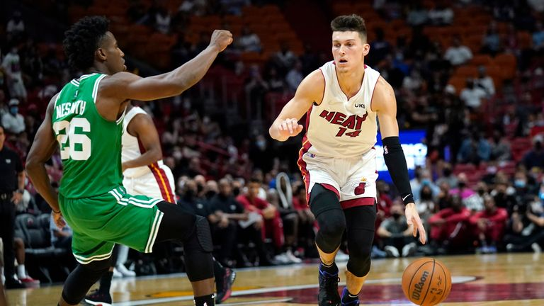 Miami Heat guard Tyler Herro (14) drives to the basket as Boston Celtics forward Aaron Nesmith (26) defends during the first half of a preseason NBA basketball game, Friday, Oct. 15, 2021, in Miami. (AP Photo/Lynne Sladky)