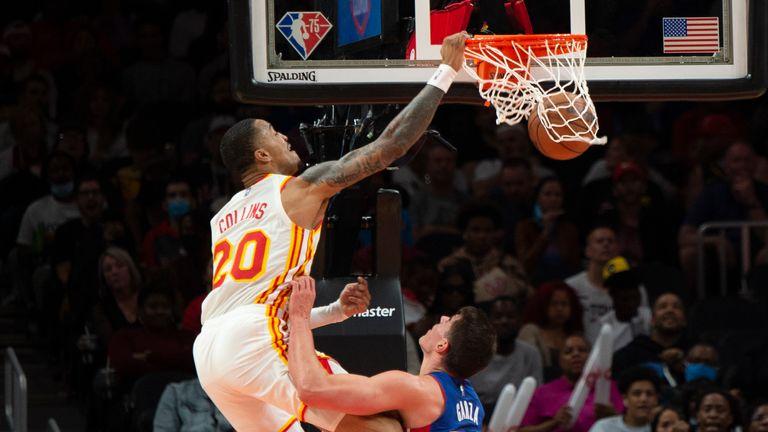 Atlanta Hawks forward John Collins (20) dunks over Detroit Pistons center Luka Garza (55) during the second half of an NBA basketball game Monday, Oct. 25, 2021, in Atlanta.