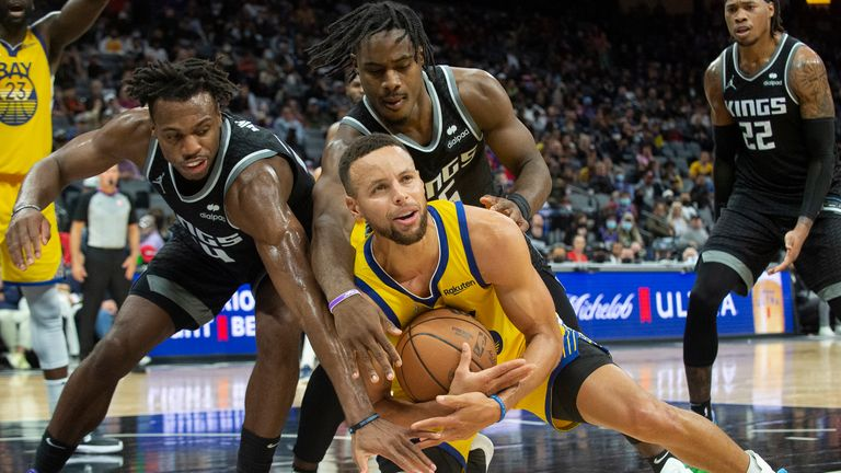 Buddy Hield and Davion Mitchell pressure Steph Curry during the game between the Sacramento Kings and Golden State Warriors